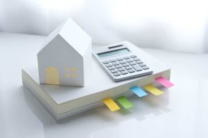 illustration of house, calculator, and notated book of estate planning advice